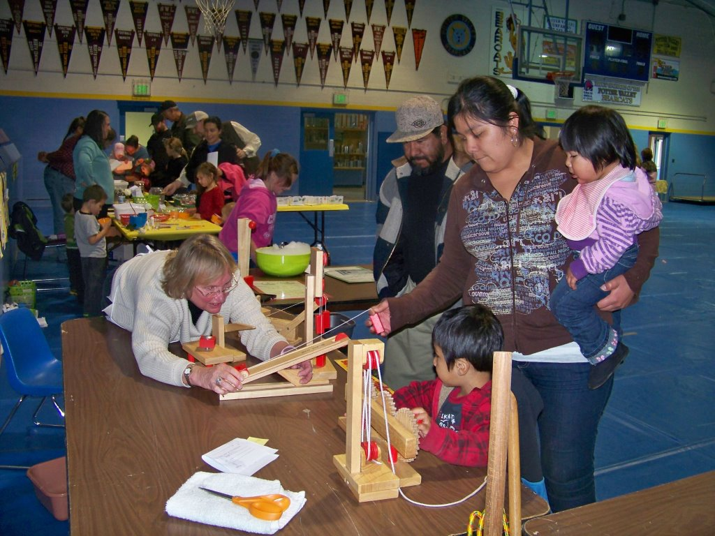 3rd grade teacher Cheri Alton demonstrates the effects of pulleys to a family during Science Night.